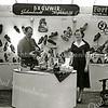 F2255<br /> Schoenenzaak Brouwer, een van oudste winkels in Sassenheim op Hoofdstraat 212. We zien hier Aad Brouwer, de vader van Theo, de huidige eigenaar. Rechts zijn schoonzus Lies, die getrouwd was met Ted, die de scepter zwaaide in de werkplaats. Ted en Lies Brouwer woonden in 'De Beukenpit' op Parklaan 72.