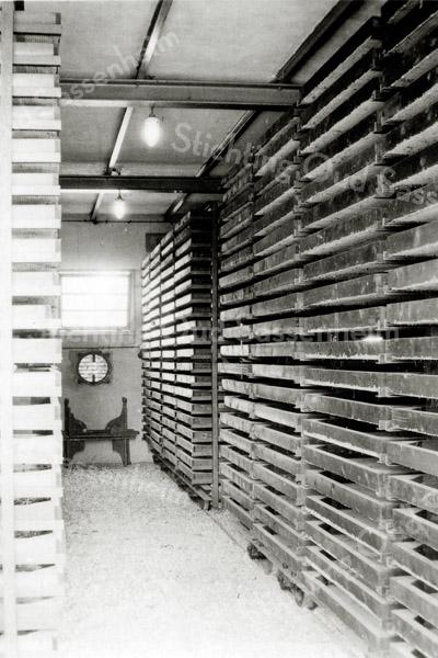 F0555c <br /> In de schuur van het bollenbedrijf van Oostveen. We zien de opgestapelde gaasbakken, met de bollen erin. Zie ook F0555a en F0555b. Foto: jaren '30.
