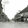 F2863 <br /> De Klapbrug. Het pand links is de kruidenierswinkel van wed. H.A. de Leeuw-Oomsen; de winkel was voor een deel ook sigarenwinkel. Wed. De Leeuw deed de zaak op 1 september 1937 over aan Barend van Loo. Deze zette de sigarenhandel voort onder de naam 'De Leeuw'; ook beheerde hij een wijndepot.<br /> Rechts zien we de winkel van de dames Lugtigheid; later kwam hier drogisterij De Hoek op de hoek van de Hoofdstraat en de Kastanjelaan.<br /> De foto is van vóór 1929. In dat jaar is de H.H. Engelbewaarderskerk gebouwd en die is op de foto niet te zien. (Vergelijk foto F0478.)