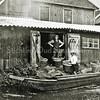 F0030 <br /> Het bollenbedrijf van Klaas Oudshoorn, achterin de Zuiderstraat. Let op de letters K.O. op de deuren en manden. De staande man is de Duitser Harold Olie, een vriend van Arie Oudshoorn. Foto: ca. 1930.