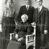 F1110 <br /> Een foto van de grootmoeder van Jan Verhoog met haar kinderen, gekleed in weduwendracht en met mopsmuts. Neeltje Verhoog-van den Boom (1868-1933) werd geboren in Woubrugge, zij woonde later in Kaag en daarna in Sassenheim.<br /> Dochter Johanna Verhoog (1898-1964) woonde in Kaag, Sassenheim en Lisse. Zoon Arie Verhoog (1900-1992) woonde in Kaag, Sassenheim, Canada en de USA. Zoon Willem Verhoog (1902-1939) woonde in Kaag en Sassenheim. Foto: ca. 1920.