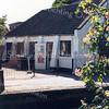 F0087a <br /> De asschuur aan de Vaartkade, waarover in de jaren negentig zoveel te doen is geweest. De schuur stamt uit de 19de eeuw en diende voor opslag van as, dat bij de bevolking werd opgehaald. De as werd via de Sassenheimervaart (die waarschijnlijk al in de 17de eeuw werd gegraven) naar Leiden vervoerd voor de fabricage van zeep. In de jaren negentig had H. Warmerdam er zijn schoenmakerij. Het pand is gesloopt in 2002. Foto: 1996.