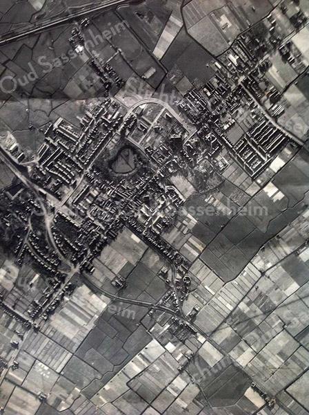 F3557<br /> Luchtfoto van Sassenheim. Van linksonder naar rechtsboven loopt de Hoofdstraat richting Sassenheim-zuid, In het midden is park Rusthoff te zien. Rechts daarvan staat de r.-k. kerk St.Pancratius. De bocht in de Parklaan is ook prachtig te zien.