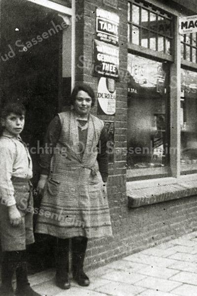 F2840<br /> De kruidenierswinkel van Wilhelmus Schrama op de Van Heemstrastraat nr. 12. Op deze foto uit 1931 zien we dochter Gré en haar broertje Dirk.