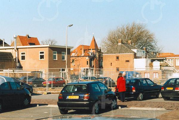 F4266<br /> <br /> Het parkeerterrein aan de Kerklaan met het zicht op de achterkant van de huizen aan de Hoofdstraat. Het pand met het torentje is makelaar Heemborgh. Foto: 2002