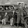F0994 <br /> Opzij van de bollenschuur van J.A. van der Voort, naast de villa Twin's Home. Vóór de auto zien we v.l.n.r.: Trees, Truus en Aad van der Voort. In de auto: Bep, Kees, Toos, Clementine en Dick van der Voort (met hoed). De auto is een Ford met het nummer H5123. Foto: jaren '30.