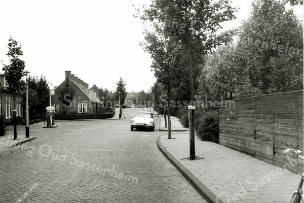 F0476 <br /> De Concordiastraat in de jaren vijftig gezien vanaf de Hoofdstraat. Links de benzinepomp met woonhuis van garagebedrijf Ep Postma, later van H. van Santen. Rechts de schutting van de tuin achter Hoofdstraat 288 waar de familie Vis-Landwer Johan woonde. In het midden, links voor de brug over de Sassenheimervaart, zien we de seniorenwoningen waar vroeger het buurtje Amerika was.
