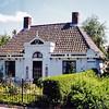 F0058 <br /> 'Het mooiste huis' van Sassenheim aan de Hoofdstraat 100 – zo kan dit prachtige pand wel betiteld worden. Met zijn bijzondere stijl en welverzorgd uiterlijk doet dit huis aan een typisch renteniershuis uit vroeger tijden denken. <br /> Van oorsprong is dit huis de portierswoning aan de rand van het grote landgoed van buitenplaats Ter Wegen. Dat landgoed strekte zich uit van de Zandsloot tot de Warmonderdam en van de grenssloot tussen Voorhout en Sassenheim tot helemaal aan de Kagerplassen! In 1840 werd het landgoed verkocht; daarbij werd een bunder grondgebied buiten de verkoop gehouden, zodat de 'heren van Ter Wegen' dit gedeelte konden gebruiken om te jagen. De portier moest ervoor zorgen dat het toegangshek en het pad goed werden onderhouden, alsmede de losplaats aan de Zandsloot.<br />  Daarna is dit pand o.a. bewoond door de fam. Faas en later door de fam. Drost. Melkslijter Koos Drost woonde in het huis erachter, nu nummer 102. Leen Drost woonde op nr. 100; hij heeft de woning door vererving verkregen. (De bijnaam 'het Drosthuisje' is hiermee verklaard.) Toen hij overleed, mocht zijn weduwe mevr. Drost-Imanse er blijven wonen totdat ze het vrijwillig zou verlaten. Op 11 oktober 1982 verkocht zij het huis op nr. 100 aan W. van Hage. Deze liet het huis eerst verbouwen, voordat hij er in 1987 in ging wonen. <br /> Foto: 1995