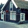 F0110 <br /> De vroegere boerderij van Willem van Rijn in ca. 1975, gelegen aan de Kerklaan. Het pand is in verval en staat op de nominatie gesloopt te worden. Links ziet men de deur en het raam van de ruimte voor de melkverwerking. Tussen het woonhuis en de stal was een poort. Daarachter was vroeger, naast de paardenstal, nog een woning, waar de vader van Willem sr. heeft gewoond. De fam. W. Roor heeft van 1962 - april 1969 in de boerderij gewoond. Daarna heeft de fam. Riny de Bruyn er nog vier jaar gewoond. Het pand is gesloopt in 1975. Uiterst links het dak van het buurtje van zes huizen aan de Kerklaan. Foto: vóór 1972.