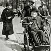 F0075 <br /> De heer Van Leeuwen (wordt vermeld bij F0074) in een rolstoel. Hij had de bijnaam 'de chef' en hij moet familie geweest zijn van Van Leeuwen van huize De Schulp. Hij was een bekende verschijning in het dorp. Hier wordt hij geduwd door Willem Bakker van de garage aan de Oude Haven. De vrouw op het trottoir is zijn zuster. Hij had twee zusters, deze waren nogal excentriek. Op de achtergrond de winkel van Verlint, het huis van Vlasveld en van Bruijnen. Foto: ca. 1935.
