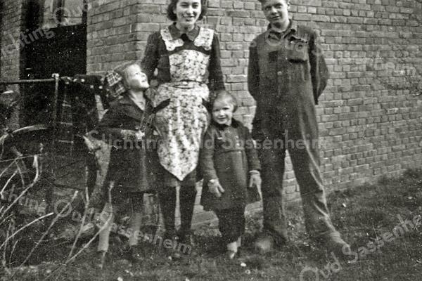 F3003<br /> Alie Berg en Freek v.d. Wilden (personeelsleden) bij de werkplaats van G. Lascaris, Hoofdstraat 234b. Links Tiny, rechts Ria Lascaris. Foto: ca. 1943.
