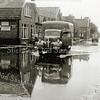 F2417<br /> Een Dodge uit 1946 van Huibert Tukker (woonde in de Molenstraat). Locatie: een overstroomde Molenstraat. Links de Essopomp van (destijd) Garage Stouten. Voor het huis staan W.J. van Biezen en zijn vrouw. Huibert Tukker staat op de treeplank. Foto: juli 1949.