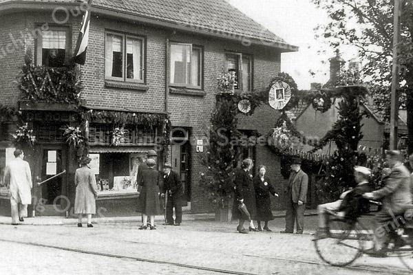 F0181 <br /> Koninginnedag 1948 of 1949. Links Arie Vos. Hij staat te praten met de 'oude' J. van Diest, de vader van mevr. Melman. Mevr. Van Duyvenbode staat met haar man en een andere dame. Uiterst links de rug van Karel van Tol. De foto is genomen aan de ingang van de Kastanjelaan. Rechts een zwaarbeladen fiets.   Foto: 1948/49.