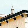 F4348d<br /> Een dakversiering, een zgn. makelaar, op het dak van een woning aan de Hoofdstraat 210. Foto: 2002.