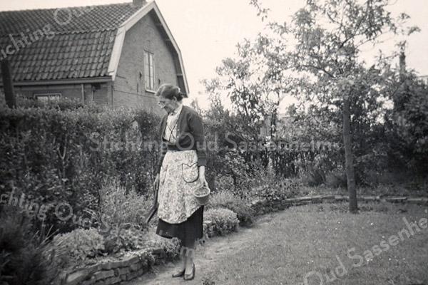 F3115<br /> Mevr. Kruijswijk achter in de tuin van woonhuis op Postwijkkade 8. Het huis links is het laatste huis van de Oude Poststraat. Daar woonde destijds de fam. Geerling. Het huis is later afgebroken. Foto jaren vijftig.