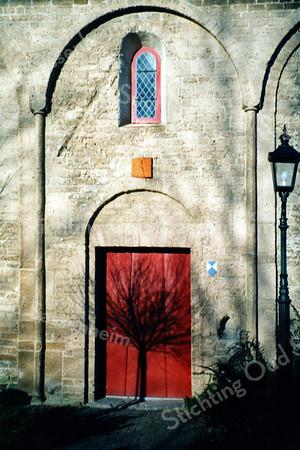 F0099 <br /> De zijdeur van de  Ned.-herv. Kerk of Dorpskerk in het romaanse gedeelte. Die deur is tijdens de restauratie in 1971 weer opnieuw aangebracht. Let op het kleine raam in de tufstenen muur met daaronder de zonnewijzer en rechtsonder het nisje voor het wijwater. De lantaarnpaal is nieuw, maar past mooi in het geheel. Ook de driedelige deur met klink en afsluitbalk is historisch en diende in vroeger jaren als beveiliging tegen geweld in oorlogstijd. Foto: 1998.
