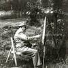 F1584 <br /> Cas Verlint (1883-1978) is bezig aan een schilderij. Hij was een bekende figuur in Sassenheim. Hij was klokkenmaker, maar men kon bij hem ook terecht voor een bril en hij was kunstschilder.
