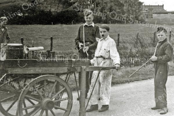 F1100 <br /> Bevrijdingsoptocht voor kinderen op 30-8-1945. V.l.n.r.: Aad, Henk en Piet van Rijn. De schilderskar is geleend van wethouder Vogelaar.