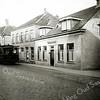F1565 <br /> De Hoofdstraat met stoomtram bij de Kerklaan. Uiterst links het huis van de fam. G. Vlasveld (afgebroken in 1933). Dan de winkel en woonhuis van W.L. Künemann, tevens depot van de stoomtram, die heeft gereden van 16 mei 1881 tot 30 december 1932. Daarnaast het snoepwinkeltje van de wed. Faas, later woonhuis van koster Klaas den Boer. Het lagere pand is van aannemer J.P. Oudshoorn. Foto: 1930.