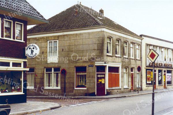 F0293 <br /> De winkel van Cas Verlint op de hoek van de Kerklaan/Hoofdstraat. De foto is genomen toen de winkel en het woonhuis al waren ontruimd, gezien de schotten voor het ene etalageraam en de andere lege etalage. Rechts daarvan het woonhuis van Ger de Boer, kosteres van de Ned.-herv. kerk (Dorpskerk). Beide panden zijn in 1975 afgebroken. De zaak van Albert Heijn daarnaast. Links op de hoek de winkel van Th.A. de Haas. (zie ook bij foto F0292) Foto: ca. 1975.