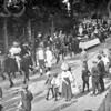 F0720a <br /> Historisch-allegorische optocht tijdens  het onafhankelijkheidsfeest in 1913. We zien hier de kop van de stoet. Links nog net een paar muzikanten van Crescendo. Daarachter begint de eerste groep. Als eerste een heraut te paard (M. v.d. Vlugt), daarachter een groepje lopende en twistende patriotten en prinsgezinden, gevolgd door de sloep met stadhouder Willem V (J. Thijs) en zijn gevolg. De foto is genomen op de Hoofdstraat ter hoogte van de r.-k. kerk waar nu de Parklaan begint. Aan de overzijde van de weg achter de bomen zien we het ijzeren toegangshek naar villa Casa Reale. Foto: 1913.