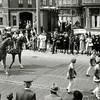 F0105 <br /> Het bloemencorso van ca. 1948. De foto is genomen op de Hoofdstraat ter hoogte van het bollenbedrijf Scheffers & Kroes NV (schuin tegenover de Bijdorpstraat). Waarschijnlijk wordt hierbij Jacoba van Beieren uitgebeeld, die met haar gemaal Frank van Borselen uitrijdt, voorafgegaan door een aantal pages. Foto: ca. 1948.