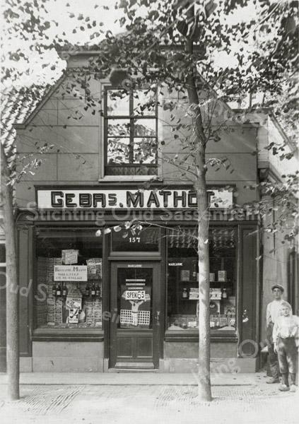 F0851 <br /> Oude winkelpand van fa. Mathôt, Hoofdstraat 157 vóór de verbouwing (rond 1920). Later kwam hier een moderne winkel met woonhuis voor Mathôt (zie foto F0852). Nu (2016) is hier al vele jaren de ABN AMRO gevestigd, op Hoofdstraat 213.<br /> <br /> Collectie Oudshoorn 080: verbouw winkelhuis Mathôt, Hoofdstraat 157, volgens de oude nummering. Foto: vóór 1921.