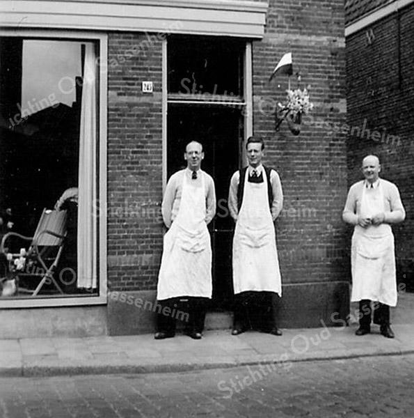 F2714<br /> De zadelmakerij en meubelhandel van Van der Meer. Guurt (links), Joop (midden) en vader Jan van der Meer rechts, voor de winkel in de Hoofdstraat (naast 't Bruine Paard).<br /> Op 15 augustus 1890 begon opa Jan van der Meer deze winkel. Hij vestigde zich als zadelmaker en rijtuigbekleder. Zoon Jan zette deze winkel voort, later samen met zijn zoons Guurt en Joop. Vanuit de rijtuigbeklederij en zadelmakerij ontwikkelde zich de behangerij en stoffeerderij en de handel in lederwaren.<br /> In november 1965 verhuisde de zaak naar het nieuwgebouwde pand naast de r.-k. kerk en naast J. Bemelman Herenmode. Sinds 2016 is het bedrijf gevestigd in de Havenpoort. De zaak wordt tegenwoordig gevoerd onder de naam 'Van der Meer Interieur' door Remco van der Meer (de vijfde generatie).