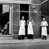 F2714<br /> De zadelmakerij en meubelhandel van Van der Meer. Guurt (links) Joop (midden) en vader van der Meer rechts, voor de winkel in de Hoofdstraat (naast Het Bruine Paard).<br /> Op 15 augustus 1890 begon Opa Jan van der Meer deze winkel. Hij vestigde zich als zadelmaker en rijtuigbekleder. Zoon Jan zette deze winkel voort, later samen met zijn zoons Guurt en Joop. Vanuit de rijtuigbeklederij en zadelmakerij ontwikkelde zich de behangerij en stoffeerderij en de handel in lederwaren.<br /> In november 1965 verhuisde de zaak naar het nieuwgebouwde pand naast de RK-kerk en naast J. Bemelman Herenmode, waar het thans nog is gevestigd. De zaak wordt tegenwoordig gevoerd onder de naam 'Van der Meer Interieur' door Remco van der Meer (de 5de generatie).