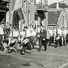 F1555 <br /> De afmars vanaf gebouw Concordia van mondharmonicavereniging Excelsior naar de jaarlijkse dodenherdenking bij het monument aan de Verlengde Vinkenweg. De opname is gemaakt op de Hoofdstraat nabij de Klapbrug. Links de winkel van Barend van Loo. De tamboer linksvoor is Klaas Overvliet, daarnaast Aadje Dannijs (geëmigreerd naar Canada). De vlaggendrager is Jan Piet Vis, rechts daarnaast (in pak) dirigent Van der Woude (?). Links de persoon met de flinke haardos is Oudshoorn; man met grote trom is Hannes Knetsch en rechts daarvan met kleine trom Tom Eikelenboom. Foto: ca. 1947.