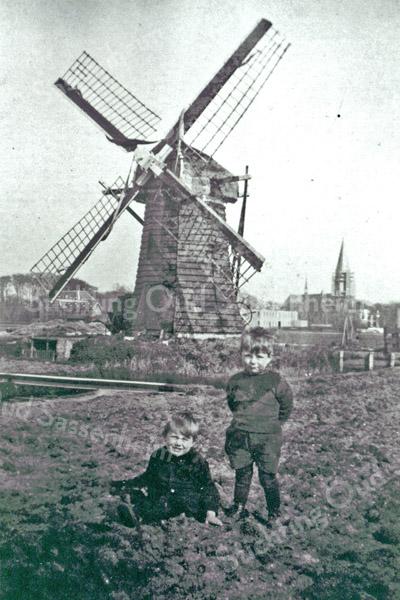 F0014 <br /> Poldermolen in de Mottigerpolder. Het is een windschepradmolen met een houten as en wieken, staande en uitslaande op de Scheisloot. Op de voorgrond Kees (links) en Piet (rechts) Oostveen. Op de achtergrond links Het Oude Koningshuys en de bollenschuur van Blinde & Batenburg (later Gebr. G.& P. Westerbeek). Rechts de bollenschuur van Van Zonneveld & Co NV en de r.k.-kerk St.Pancratius, waarvan de toren nog in de steigers staat. Daarvóór villa Casa Reale. Foto: 1929.