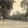 F0789 <br /> Tegenover de Charbonlaan staan de twee pilaren aan de ingang van park Rusthoff, die Oudshoorn ontwierp en bouwde voor Jan Adam Charbon. Ook het muurtje is toen gebouwd. De palen staan precies voor de rode loper van tegenwoordig. Rechts de kleine woningen aan Menneweg, nu J.P. Gouverneurlaan. Foto: vóór 1921.<br /> <br /> [Collectie Oudshoorn 078: Ingang wandelpark Rusthoff.]