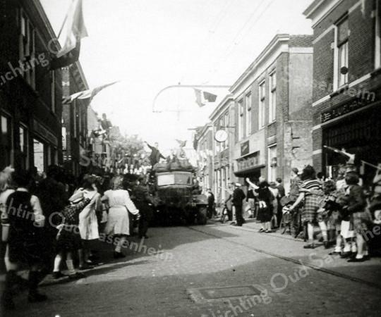 F0362c <br /> Bevrijding mei 1945. Rechts de winkel van Bruijnen, Hoofdstraat 264 met daarnaast  de snoepwinkel van Jamin. Links de winkel van Van der Meer (leerhandel enz.) Foto: 1945.