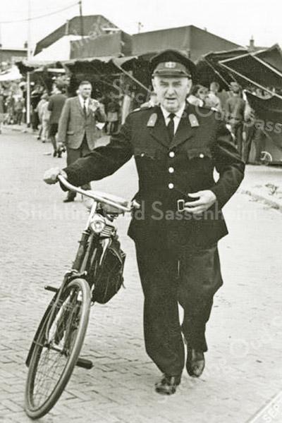 F3876<br /> Adjudant van der Laan hoofd van de politie in Sassenheim loopt hier in 1961 met zijn fiets aan de hand over de kermis.