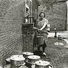 F3302<br /> Dora Verkleij-van Diemen aan het water pompen bij de boerderij de Bonte Koe. Foto: 1954.