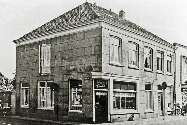 F0685 <br /> De winkel van Casper Verlint, horlogemaker en kunstschilder, op de hoek van de Hoofdstraat/Kerklaan, met links het woonhuis. Rechts naast de winkel is het woonhuis van Klaas de Boer, koster van de herv. kerk.  Uiterst rechts is nog net de winkel van Albert Heijn zichtbaar. De winkel van Cas Verlint en het woonhuis zijn in 1975 afgebroken. Daarna is daar de winkel van Albert Heijn verrezen. Nu, in 2016, zijn er appartementen met winkels eronder.