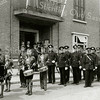 F1568 <br /> Mogelijk is deze opstelling t.g.v. van de prijsuitreiking van de (interlokale) schietwedstrijden, die de jubilerende politieschietvereniging Wilhelmina op 2 juli 1937 hield. Hieraan deden niet alleen politiemannen mee, maar ook burgerleden van de vereniging en leden van de BVL (Bijzondere Vrijwillige Landstorm). Zie Leidsch Dagblad van 2 juli 1937.<br /> Vooraan staat Adrie Elst (zoon van Joseph Elst) met vlag. De tweede tamboer van links is een jongen van Caspers; daarnaast een jongen van Berg (KJC). De tweede politieman van links is dhr. Joseph Elst (naar hem is de Joseph Elststraat genoemd). Op het bordes staat burgemeester J.P. Gouverneur; links van hem dhr. Los (gemeentesecretaris) en rechts de heren Vlasveld en Melman. Foto: 1937.