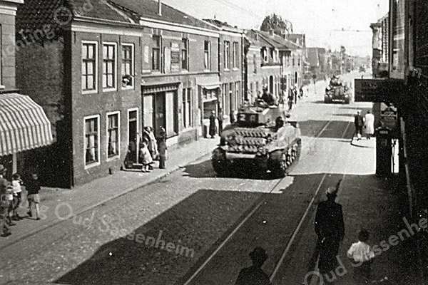 F0178 <br /> De intocht van de Canadese troepen in mei 1945. De belangstelling is minimaal. De foto is genomen aan de noordelijke kant van de Klapbrug (Hoofdstraat). Links het woonhuis van de fam. Blom en de winkels van Van der Staak en van J. Rhijnsburger. Foto: 1945.