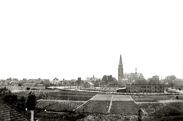 F3713<br /> Een sfeervol plaatje, genomen vanaf het dak van de Hygia. Links op de foto het dak van het woonhuis van fam. Ter Meer v.h. van Janus Schoo Menneweg 71-73. <br /> In het midden zien we de St. Pancratiuskerk met links daarvan de  r.-k. St. Antoniusschool en vóór de kerk de bollenschuur van Baartman & Koning. Helemaal links de boerderij van Langeveld. De Parklaan is al aangelegd.