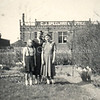 F3118<br /> Achter in de tuin bij de fam. Kruijswijk, Postwijkkade 8. Moeder Kruijswijk met haar dochters. Op de achtergrond de bollenschuur van C.J. Speelman. Foto jaren vijftig.