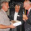 F3410<br /> Aanbieding van de taart aan de 700ste (?) donateur. Rechts staat Hans Walenkamp, voorzitter van de Stichting Oud Sassenheim. In het midden staat Ton van der Wiel.