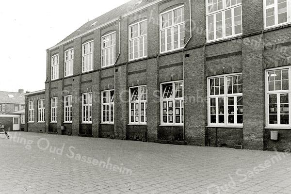 F1367b <br /> Zijaanzicht en speelplaats  van de r.-k. jongensschool aan de Hoofdstraat. Zie ook foto 1367a. Op de achtergrond de huizen van Pancraszicht.