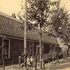 F0784 <br /> Het begin van de Menneweg (nu J.P. Gouverneurlaan); rechts op de achtergrond zien we de Hoofdstraat. Links staat een zestal arbeiderswoningen die in opdracht van F. Haver in 1899 werden gebouwd. De bouwvallig geworden woningen werden in 1964 gesloopt.  Hier werd later de Rabobank gebouwd. Foto: vóór 1921.<br /> <br /> [Collectie Oudshoorn 015: zes arbeiderswoningen F. Haver 1899 (J.P. Gouverneurlaan).]