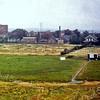 F0304 <br /> Gezicht op de achterzijde van de bebouwing aan de Teijlingerlaan vanuit het reuzenrad, dat tijdens de kermis van 1972 was opgesteld op het feestterrein aan de Willibrorduslaan/Frankenhorst. De rechterzijde van de Frankenhorst was toen nog niet bebouwd. Uiterst links de vroegere bollenschuur van Westerbeek. Rechts daarvan de ruïne van Teylingen en de achterkant van de bebouwing langs de Teijlingerlaan met de hoge pijp van de vroegere stoomwasserij Hollandia en de bollenschuur van Theo v.d. Vlugt. Op de voorgrond het lege terrein waar plan Teylingen later zal verrijzen. Foto: 1972.