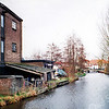 F0325 <br /> Gezicht op de Sassenheimer Vaart. Links de vroegere bollenschuur van B.J.Kapteyn & Zoon, nu modelmakerij Friedhoff aan de Vaartkade. Op de achtergrond de brug in de Concordiastraat met de huizen langs de Molenstraat. De foto is genomen vanaf het terrein van de Kringloopwinkel aan de Bijweglaan, dit is enigszins te zien op het zeil van de aanhangwagen rechts. Foto: 1998.