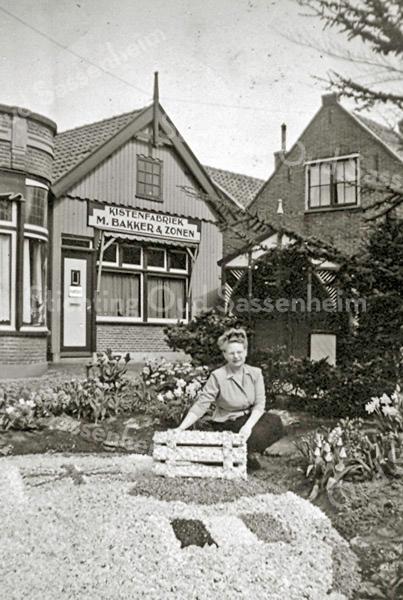 F2421<br /> Mevr. Hen Bergman-Bakker, de zus van Jan Bakker, zit bij een bloemenmozaïek voor het kantoor van Kistenfabriek Bakker aan de Hoofdstraat. Links is nog een stukje van de pastorie van de oude  gereformeerde kerk te zien.