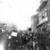 F4008a<br /> Kort na de bevrijding wordt de NSB sigarenhandelaar de Jong van de Teylingerlaan opgebracht door mensen van de ondergrondse verzetsbeweging en tijdelijk opgesloten in de bijgebouwen van hotel 'Het Bruine Paard'. Vooraan loopt dhr. Stoute, daarachter (met bord) dhr. de Jong. Foto:1945