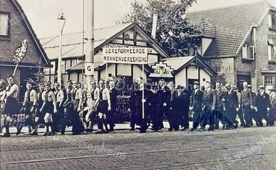 F0047 <br /> Optocht ca 1938, waarschijnlijk ter gelegenheid van het 40-jarig regeringsjubileum van koningin Wilhelmina. Voorop voetbalclub Ter Leede en daarachter de Gereformeerde Mannenvereniging. Bij Ter Leede loopt Theo Engberts met het vaandel, daarachter Adriaan Verbree, Siem Eikelenboom, Gep Perfors en Henk van Loo. Verder zijn Henk Perfors en Bert van Breda te herkennen. Bij de mannenvereniging loopt met spandoek links W. v.Diggele en rechts H.G. v.Teijlingen. Daarachter Bas v.d.Sijs (lange man) en de 4e man rechts (zonder hoed en met bril) is W.Verhoog, dan volgen Piet Oudshoorn en B. Verhoef (?). De lange rijzige man zou J. Dekker uit Warmond kunnen zijn. Helemaal achteraan loopt H.L. Boter (uiterst rechts). In het midden op de achtergrond tentoonstellingsgebouw Bloemlust. Dit stond tegenover de Willem warnaarlaan en werd ook Monte Carlo genoemd. Dit in verband met het verhandelen van bloembollen in het voorjaar, nog voor het rooien van de bollen. Foto: ca. 1938.