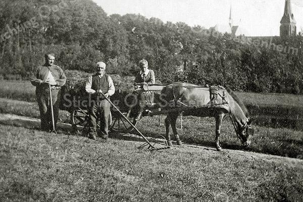F1242 <br /> De persoon met hark is Kees v.d. Berg. Op de wagen zit Leo Eduard Kruijff in de tuin van Het Oude Koningshuys. De foto is genomen tussen 1913 en 1928. Dit is te zien aan de oude toren van de St. Pancratiuskerk en het reeds verhoogde engelenkoor.