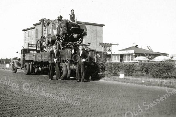 F0136 <br /> Een koets uit de koninklijke stallen wordt op een vrachtwagen getransporteerd. Rechts de eerste 'Uiver' met het puntdak. Achter de vrachtwagen de bollenschuur van W.J. Eldering & Zn. Bovenop de bok van de koets zit een begeleider. Links van de koets nog een koetsier of begeleider. Rechts Maarten van Zoen. Foto: 1938.